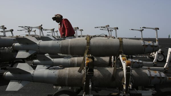 A U.S. sailor works with bombs being prepared for loading on military jets on the flight deck of the USS Carl Vinson aircraft carrier in the Persian Gulf, Thursday, March 19, 2015 - Sputnik International