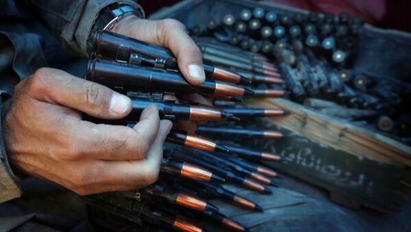 A fighter prepares an ammunition belt. - Sputnik International