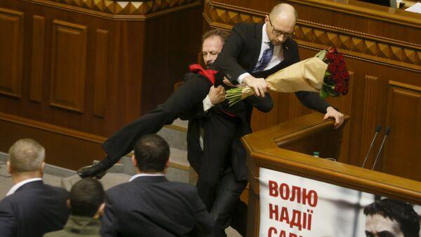 Rada deputy Oleg Barna removes Prime Minister Arseny Yatseniuk from the tribune, after presenting him a bouquet of roses, during the parliament session in Kiev, Ukraine, December 11, 2015 - Sputnik International