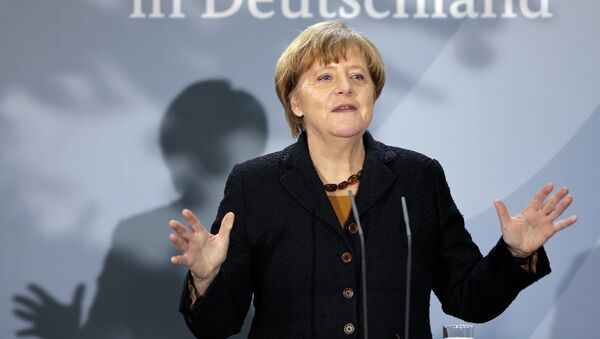 German Chancellor Angela Merkel delivers a speech during a reception at the chancellery in Berlin, Germany, Monday, Dec. 7, 2015 to mark the 60th. anniversary of the arrival of the first migrant workers in Germany. Slogan reads 'in Germany'. - Sputnik International
