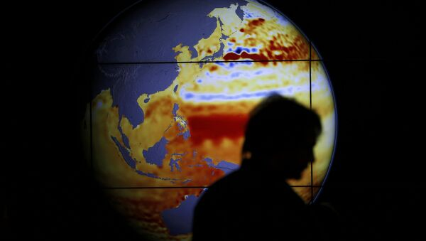 A woman walks past a map showing the elevation of the sea in the last 22 years during the World Climate Change Conference 2015 (COP21) at Le Bourget, near Paris, France, December 11, 2015 - Sputnik International