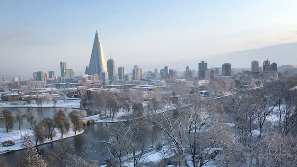 The 105-story pyramid-shaped Ryugyong Hotel towers over residential apartments and snow covered trees and fields on Thursday Dec. 3, 2015, in Pyongyang, North Korea where the winter season has started - Sputnik International