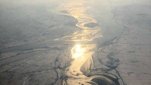 In this Friday, Nov. 27, 2015, photo, which was taken from an airplane approaching Pyongyang, light from the evening sun is cast on a river flowing through snow covered farm fields in North Korea - Sputnik International
