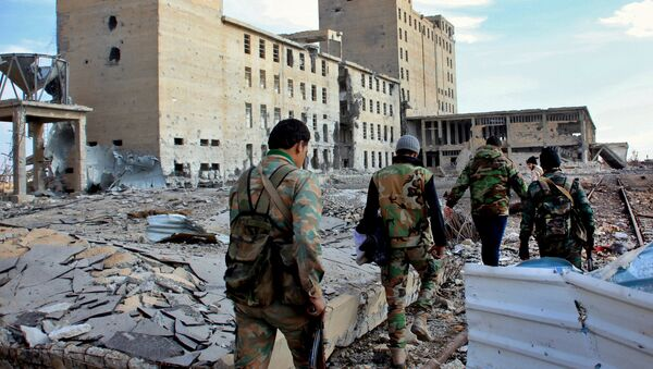 Syrian army soldiers patrol near a building previously used for storing seeds in the countryside of Deir Hafer, a former bastion of Islamic State group, near the northern Syrian city of Aleppo on December 2, 2015 - Sputnik International