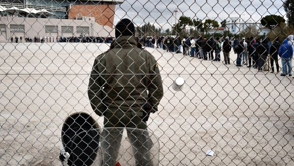 A riot policeman stands guard at a temporary housing facility for migrants nad refugees located in a former Olympic hall in Faliro suburb of Athens on December 11, 2015. - Sputnik International