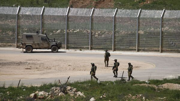 Israeli soldiers walk near a fence in the Israeli occupied Golan Heights on the border with war-torn Syria - Sputnik International