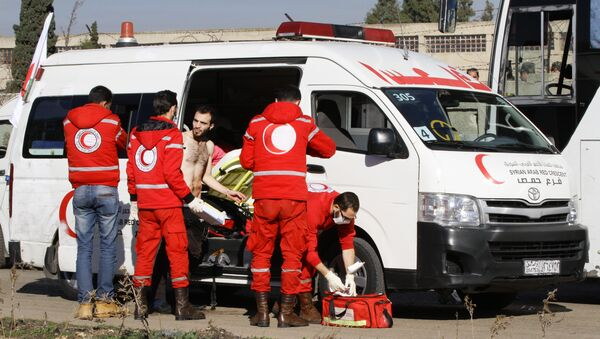 Members of the Syrian Red Crescent give aid to an injured man in the district of Waer in the central city of Homs on December 9, 2015 as hundreds of civilians and Syrian rebel forces began evacuating the last opposition-held district under a deal with the Syrian regime - Sputnik International