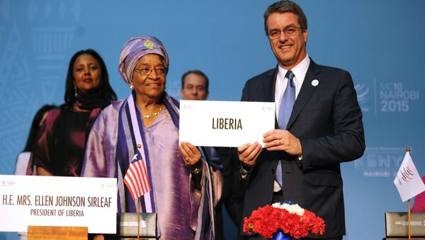 Liberian President Ellen Johnson-Sirleaf (L) holds up an identification plaque alongside World Trade Organisation (WTO) Director General Roberto Azevedo in Nairobi on December 16, 2015, during Liberia's accession to the WTO at the tenth ministerial conference - Sputnik International