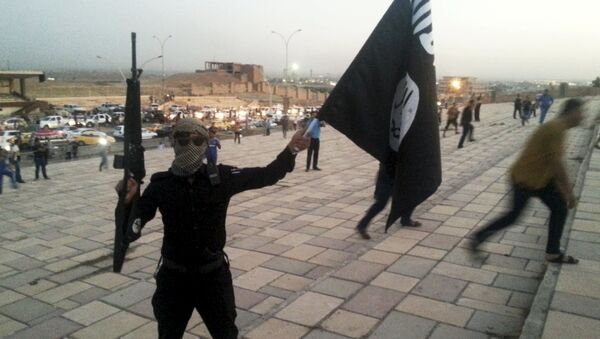 A fighter of Daesh holds an ISIL flag and a weapon on a street in the city of Mosul, Iraq, in this June 23, 2014. - Sputnik International