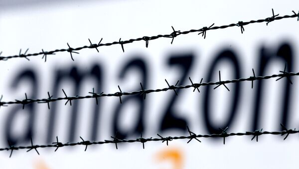 The internet trader Amazon logo is seen behind barbed wire at the company's logistic center in Rheinberg,Germany, Tuesday, Feb.19, 2013. - Sputnik International