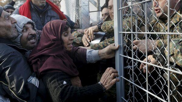 Syrian refugees struggle to enter Macedonia through a narrow border crossing as Macedonian policemen try to shut a metal gate near to the Greek village of Idomeni December 4, 2015 - Sputnik International