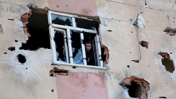 A man looks out of a building which was damaged during the security operations and clashes between Turkish security forces and Kurdish militants, in Sur district of Diyarbakir, Turkey - Sputnik International