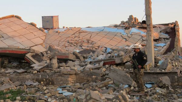 A member of the Iraqi security forces stands in the rubble of destroyed buildings in the rural Husayba al-Sharkiya area, east of Anbar province's capital Ramadi, as they undertake military operations to attack Islamic State (IS) group positions on December 20, 2015. - Sputnik International