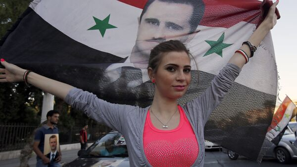 A Syrian girl holds her national flag bearing a portrait of Syria's President Bashar al-Assad - Sputnik International