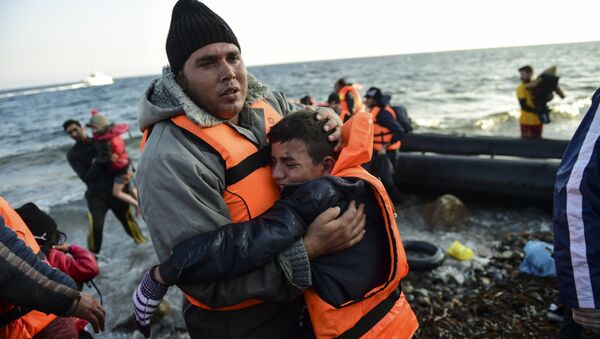 Peopl react after arriving on the Greek island of Lesbos along with other migrants and refugees, on November 17, 2015, after crossing the Aegean Sea from Turkey - Sputnik International