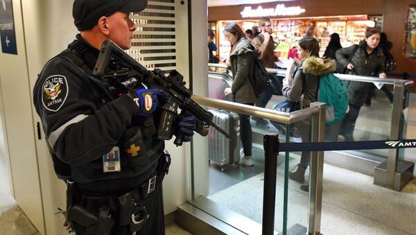 An Amtrak Police officer watches passengersas they board a train at Penn Station on November 24, 2015 in New York. After a string of terror attacks in several countries, the US government issued a worldwide travel alert warning American citizens of increased terrorist threats - Sputnik International