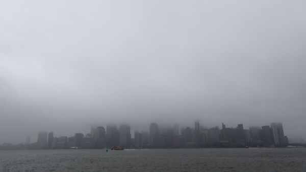 A boat chugs along the Hudson River as fog and clouds blanket over the New York City Skyline seen from Liberty State Park, Wednesday, Dec. 23, 2015, in Jersey City, N.J - Sputnik International