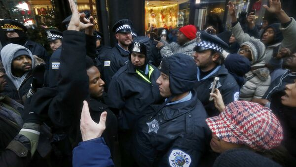 Demonstators hold their hands up in front of Chicago Police officers during protest of last year's shooting death of black teenager Laquan McDonald by a white policeman and the city's handling of the case in the downtown shopping district of Chicago, Illinois, November 27, 2015 - Sputnik International