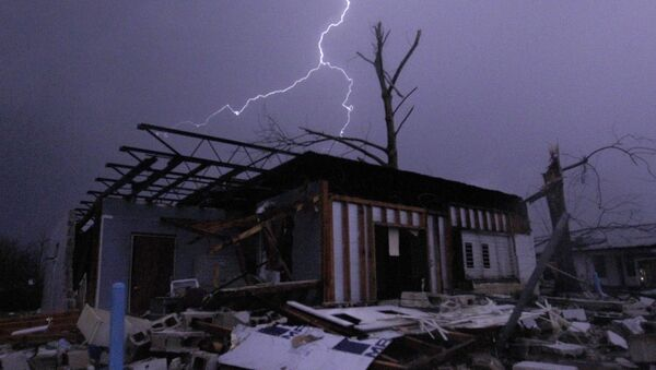 Lightning illuminates a house after a tornado touched down in Jefferson County, Ala., damaging several houses, Friday, Dec. 25, 2015, in Birmingham, Ala. A Christmastime wave of severe weather continued Friday. - Sputnik International