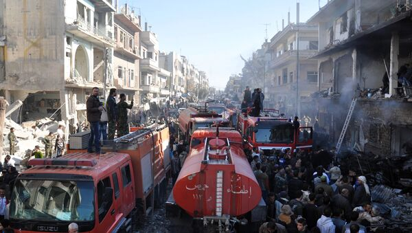 Syrians gather around fire-engines at the site of two car bomb attacks in the al-Zahraa neighbourhood of the central Syrian city of Homs on December 28, 2015. - Sputnik International