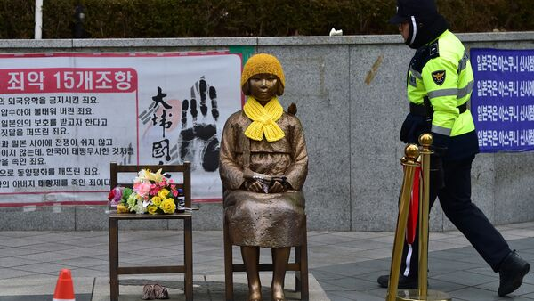 A South Korean policeman walks past a statue (C) of a teenage girl in traditional costume called the peace monument for former comfort women who served as sex slaves for Japanese soldiers during World War II, in front of the Japanese embassy in Seoul on December 29, 2015. - Sputnik International