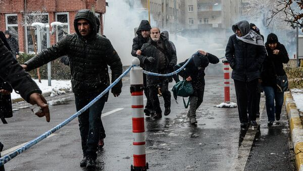 Peoples' Democratic Party (HDP) MP Ertugrul Kurkcu (back L 2nd) and protesters run away as Turkish police officers use tear gas to disperse the crowd on December 31, 2015 in Diyarbakir, during a demonstration after a curfew was partially lifted from the city on December 30 - Sputnik International