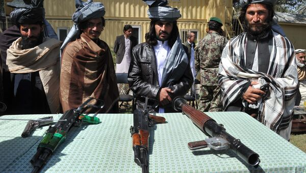 Former Taliban fighters look on as they stand alongside their weapons in Jalalabad, the capital of Nangarhar province on March 19, 2014 - Sputnik International