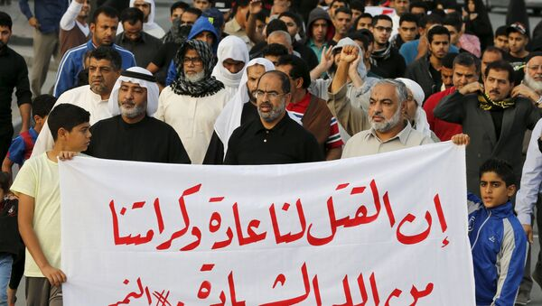 Protesters holding a banner saying Death is normal to us and our dignity from God is martyrdom take part in a protest against the execution of Saudi Shi'ite cleric Nimr al-Nimr by Saudi authorities, in the village of Sanabis, west of Manama, Bahrain January 2, 2016 - Sputnik International