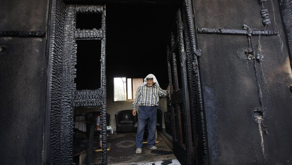 FILE - In this July 31, 2015 file photo, a Palestinian inspects a house after it was torched in a suspected attack by Jewish settlers, killing an 18-month-old Palestinian child and his parents, at Duma village near the West Bank city of Nablus - Sputnik International