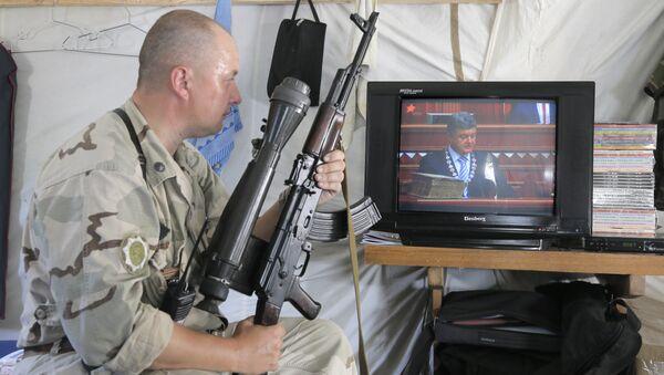 Ukrainian soldier watches the inauguration ceremony of Ukrainian President-elect Petro Poroshenko on TV in a tent at the Ukraine's Army position close to Slovyansk, Ukraine, Saturday, June 7, 2014 - Sputnik International