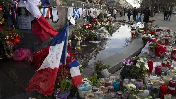 People stand next to the makeshift memorial in tribute to the victims of the Paris terror attacks, on January 4, 2016, at the Place de la Republique in Paris. - Sputnik International