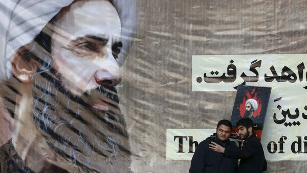 Iranian men take a selfie with a poster of Sheikh Nimr al-Nimr, a prominent opposition Saudi Shiite cleric, who was executed last week by Saudi Arabia. - Sputnik International