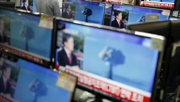 A sales assistant watches TV sets broadcasting a news report on North Korea's nuclear test, in Seoul, January 6, 2016 - Sputnik International