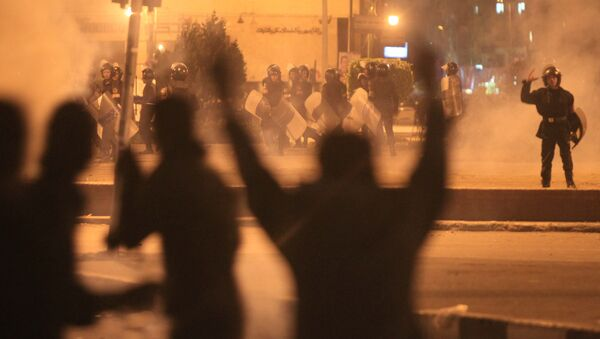 Egyptian protesters gesture as they clash with riot police at Cairo's landmark Tahrir Square on November 19, 2011, as Egyptian police fired rubber bullets and tear gas to break up a sit-in among whose organisers were people injured during the Arab Spring which overthrew veteran president Hosni Mubarak - Sputnik International