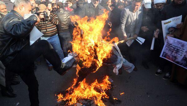 Followers of Shiite cleric Muqtada al-Sadr burn an effigy of King Salman of Saudi Arabia as they hold posters of Sheik Nimr al-Nimr during a demonstration in Baghdad, Iraq. - Sputnik International