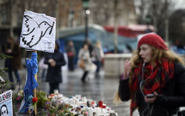 A picture taken on January 7, 2016 shows a woman standing in front of a makeshift memorial for the victims of Paris attacks at the Place de la Republique in Paris. - Sputnik International