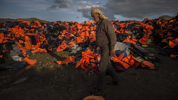 A man walks across piles of life jackets used by refugees and migrants to cross the Aegean sea from the Turkish coast which remained stacked on the Greek eastern island of Lesbos, Wednesday, Dec. 2, 2015. - Sputnik International