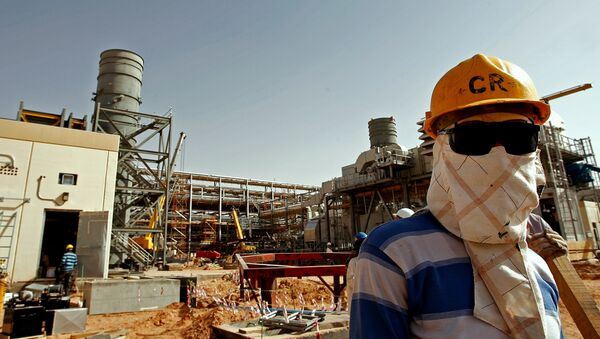 An Asian worker covers his face to protect it from the dust and the blazing sun at the site of Saudi Aramco's (the national oil company) Al-Khurais central oil processing facility under construction in the Saudi Arabian desert, 160 kms east of the capital Riyadh (File) - Sputnik International
