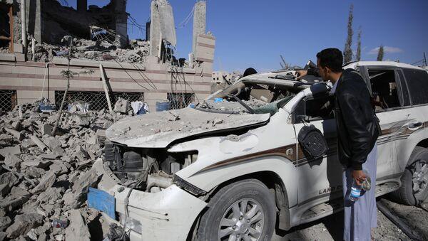 A man inspects his car damaged by Saudi-led airstrikes in Sanaa, Yemen, Friday, Jan. 8, 2016 - Sputnik International