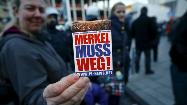A supporter of the anti-immigration right-wing movement PEGIDA (Patriotic Europeans Against the Islamisation of the West) holds up a sticker for a photo during a demonstration rally in Cologne, Germany January 9, 2016. The sticker reads, Merkel must go!. - Sputnik International