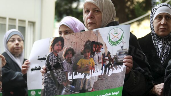 A woman holds a poster during a sit-in organized by the Sunni Al Jama'a al-Islamiya group, calling for the lifting of the siege off Madaya in front of the International Committee of the Red Cross (ICRC) in Beirut, Lebanon January 8, 2016 - Sputnik International