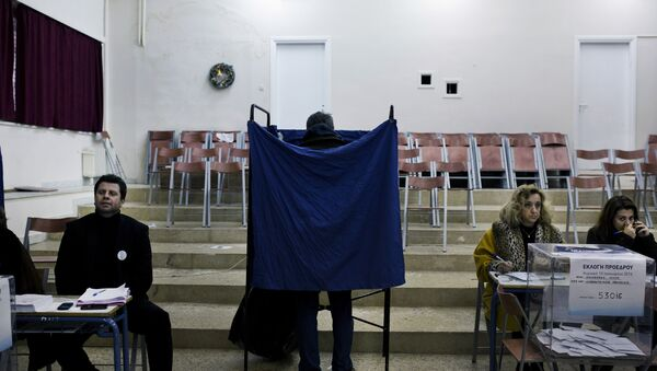 A man prepares his vote in a voting booth prior to casting his ballot in an election for the leadership of Greece's conservative New Democracy party, at a polling station in Athens on January 10, 2016 - Sputnik International