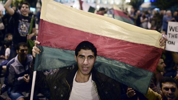 A man holds the flag of the Syrian Kurdish Democratic Union Party (PYD) - Sputnik International