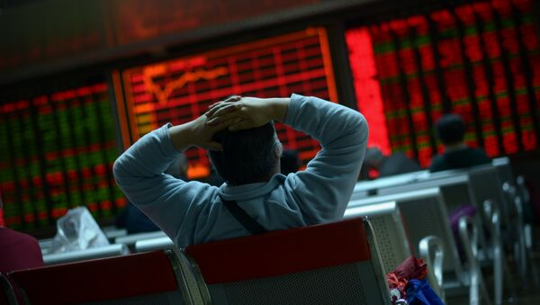 An investor looks at screens showing stock market movements at a securities company in Beijing on January 8, 2016 - Sputnik International