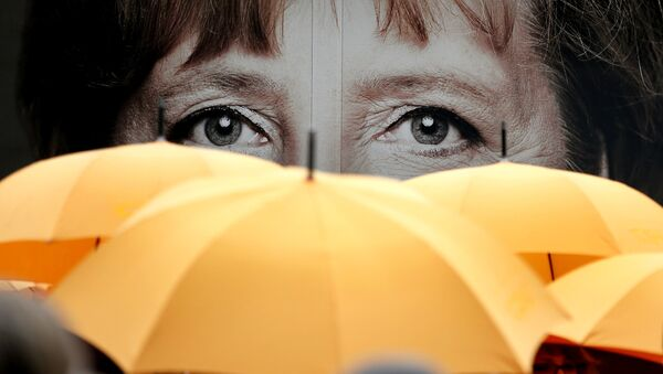 Supporters of the Christian Democratic Union (CDU) hold umbrellas in front of a giant portrait of German Chancellor Angela Merkel during an election campaign event in front of the party's headquarter in Berlin, Germany, Monday, Sept. 16, 2013. - Sputnik International