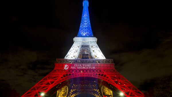 A photo taken on November 17, 2015 in Paris shows the Eiffel Tower illuminated with the colors of the French national flag in tribute to the victims of the November 13 Paris terror attacks. - Sputnik International
