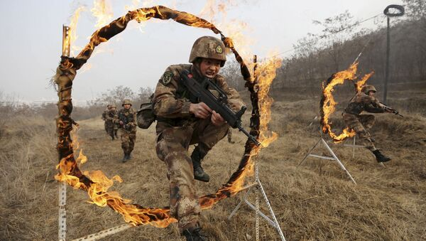 Soldiers of People's Liberation Army (PLA) Lanzhou Military Region jump through a burning obstacle during a training session at a military base in Tianshui, Gansu province, China, January 6, 2016 - Sputnik International