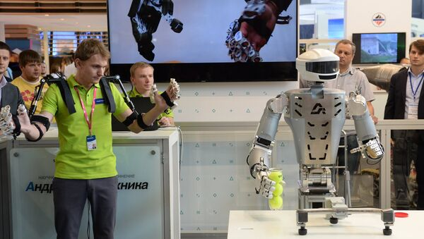 An employee of Androidnaya Teknika demonstrates a robot's operation at the V Innoprom International Industrial Exhibition in Yekaterinburg. File photo - Sputnik International