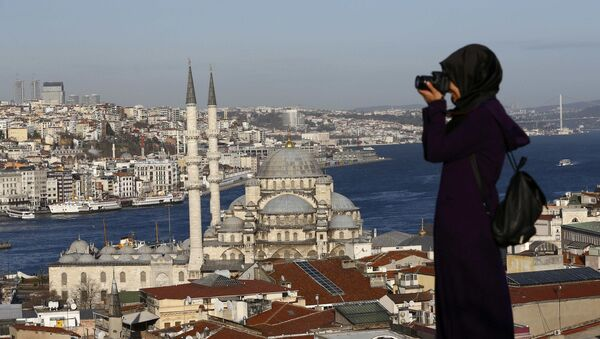 A woman takes photographs in front of the New Mosque by the Bosphorus strait in Istanbul, Turkey January 12, 2016 - Sputnik International