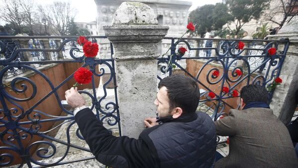 Men place flowers at the Obelisk of Theodosius, the scene of the suicide bomb attack, at Sultanahmet square in Istanbul, Turkey January 13, 2016. - Sputnik International